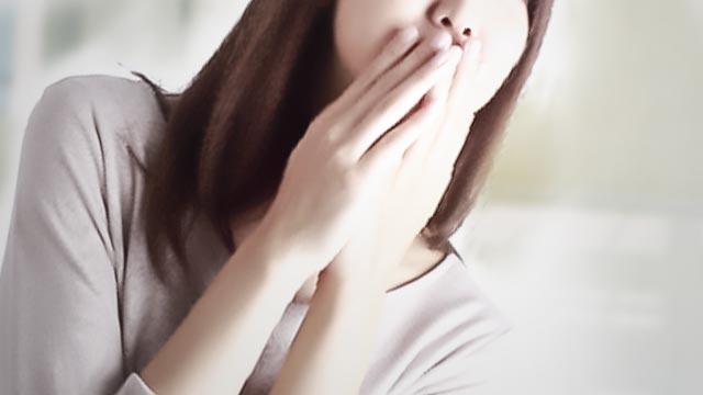 口に両手をあて口臭を気にする女性