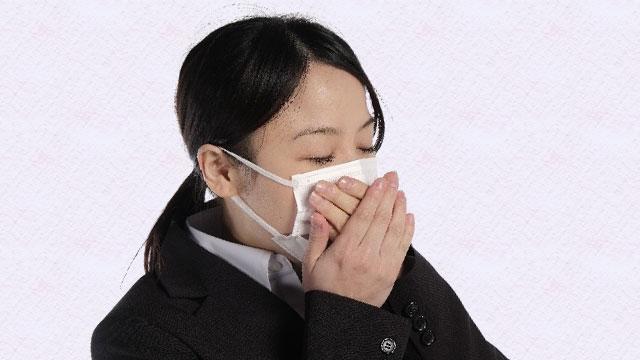 マスクをしながら口をおさえる女性
