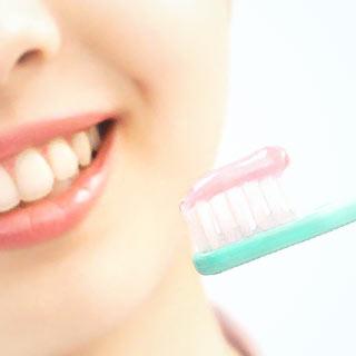 歯ブラシに塗られた歯磨き粉と女性の歯