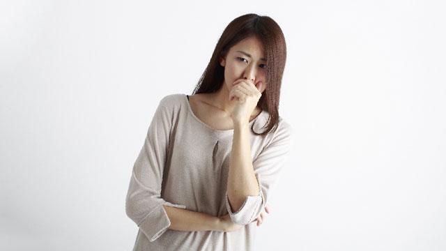 口を手で覆っている女性