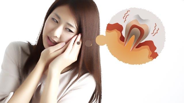 歯が痛くて頬に手をそえる女性