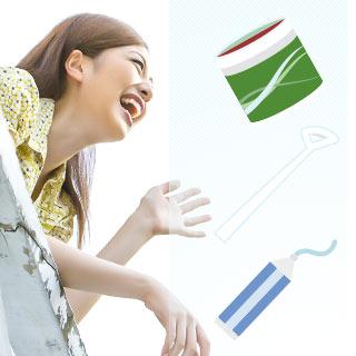 笑顔の女性とボトルガムと舌苔取と歯磨き粉